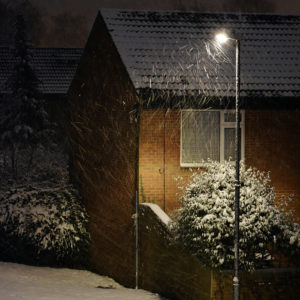 House under a street light in winter with snow on the ground